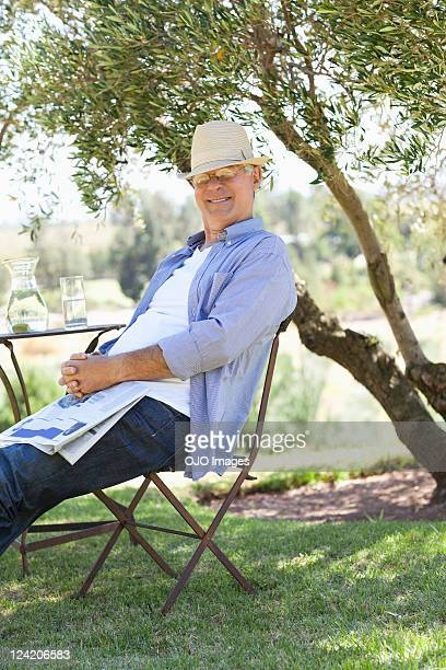 Portrait of smiling senior man with newspaper in lawn
