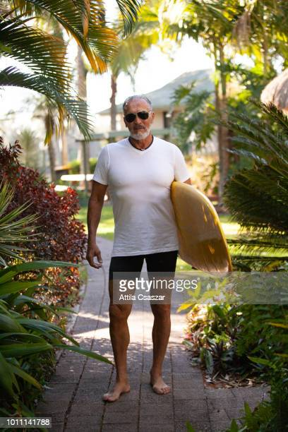 portrait of smiling senior man with surfboard by palmtrees - sunshine coast australia stock pictures, royalty-free photos & images