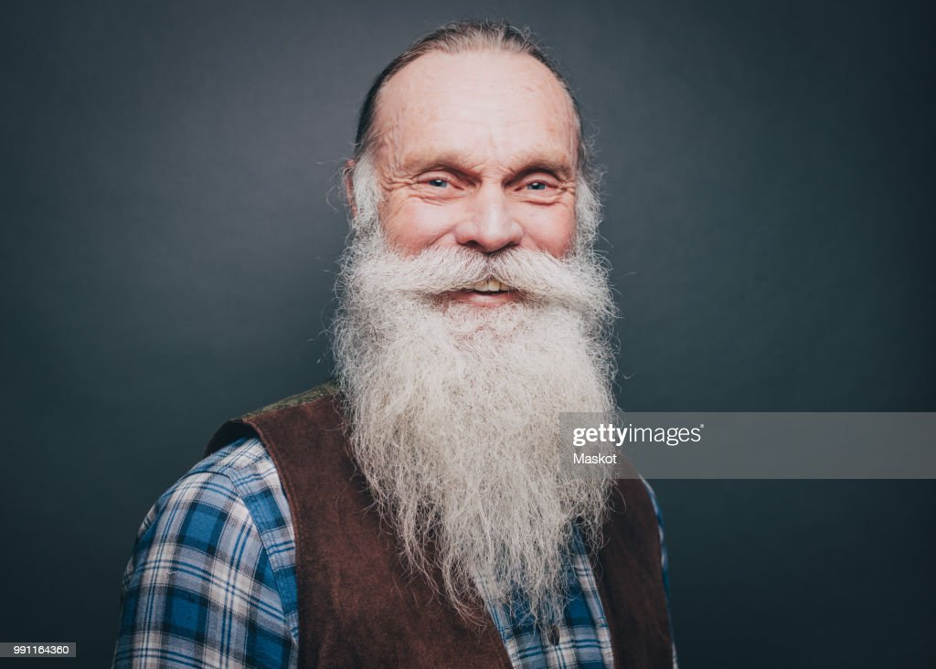 Portrait of smiling senior man with white beard and mustache against gray background : Stock Photo