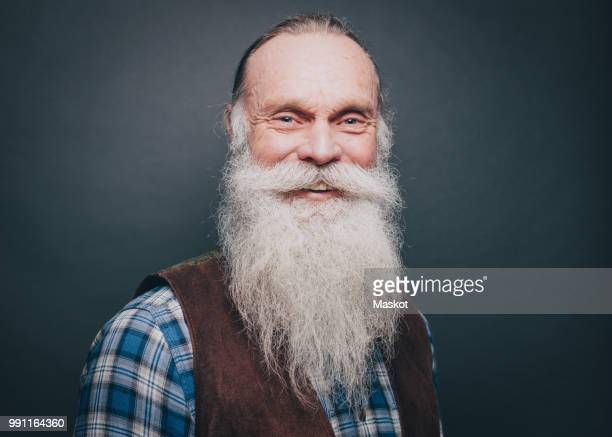 portrait of smiling senior man with white beard and mustache against gray background - lang haar stockfoto's en -beelden