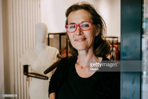portrait of smiling senior owner standing in store - capelli neri foto e immagini stock