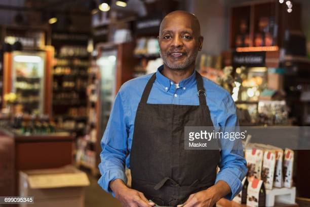 portrait of smiling senior owner standing in store - apron stock pictures, royalty-free photos & images