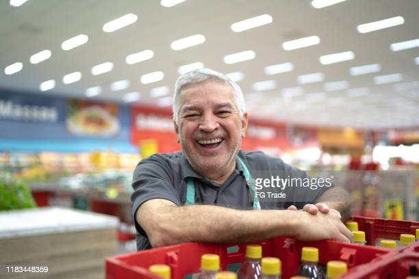 portrait of smiling senior supermarket employee - convenience stock pictures, royalty-free photos & images