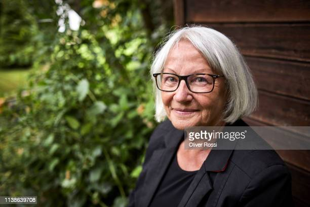 portrait of smiling senior woman at garden shed - black blazer stock pictures, royalty-free photos & images