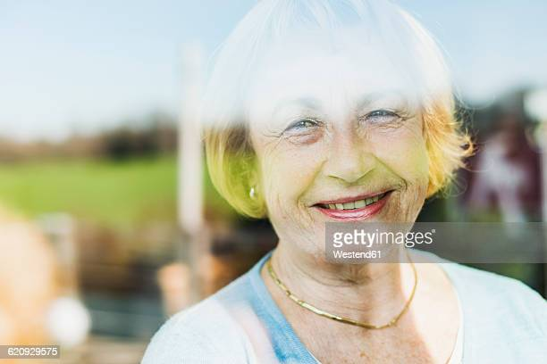 Portrait of smiling senior woman behind windowpane