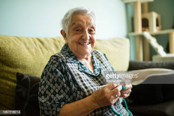 Portrait of smiling senior woman crocheting on the couch at home