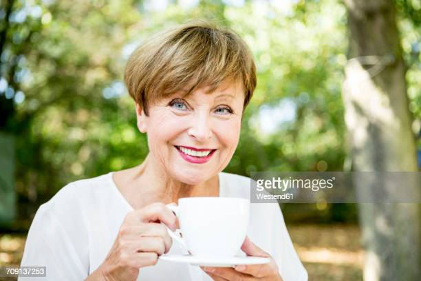 portrait of smiling senior woman drinking cup of coffee outdoors - 65 69 jahre stock-fotos und bilder