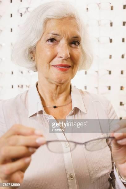 portrait of smiling senior woman holding eyeglasses at store - eine seniorin allein stock-fotos und bilder