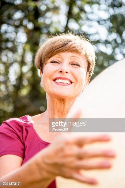 portrait of smiling senior woman holding fitness ball outdoors - gymnastique au sol photos et images de collection