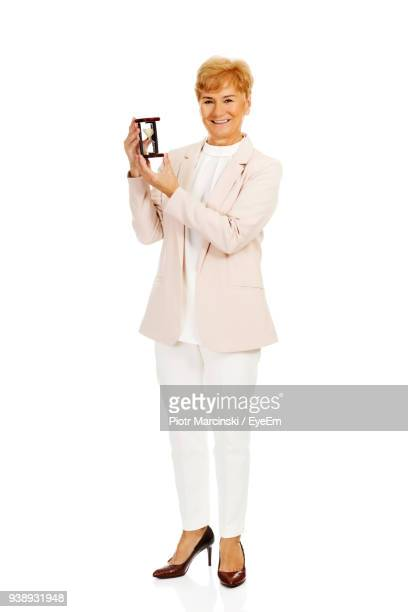 Portrait Of Smiling Senior Woman Holding Hourglass Against White Background