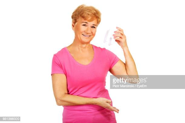portrait of smiling senior woman holding molar teeth against white background - molar stock pictures, royalty-free photos & images