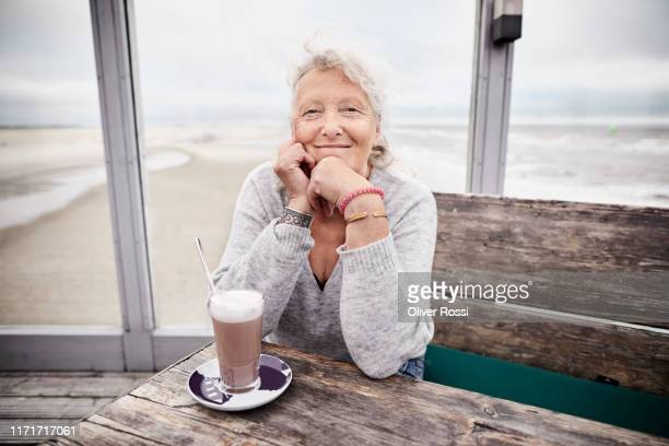 portrait of smiling senior woman in a cafe by the sea - senior women stock pictures, royalty-free photos & images