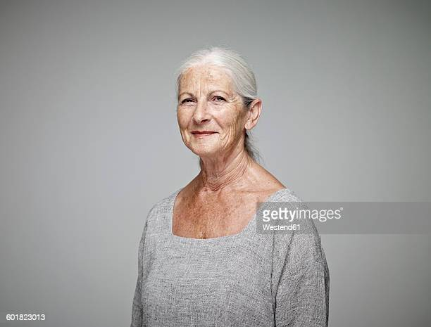 portrait of smiling senior woman in front of grey background - old woman stock pictures, royalty-free photos & images