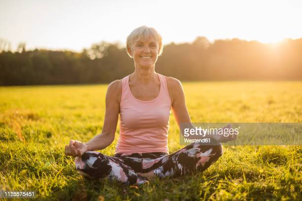 portrait of smiling senior woman in lotus position on rural meadow at sunset - sportlichkeit stock-fotos und bilder
