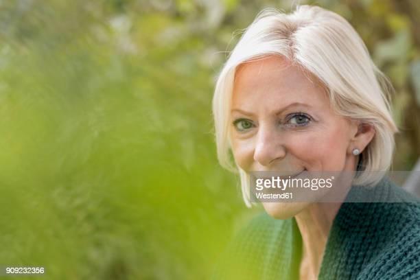 portrait of smiling senior woman in nature - eine seniorin allein stock-fotos und bilder