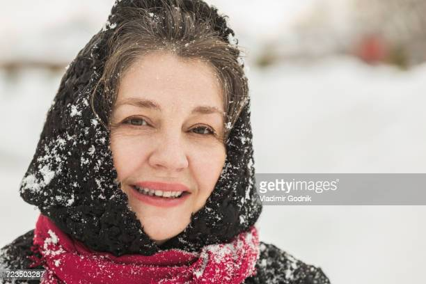 Portrait of smiling senior woman in winter wear covered with snow