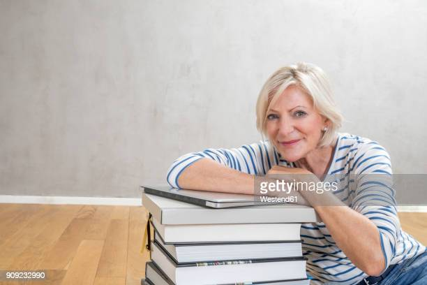 Portrait of smiling senior woman leaning on stack of books and laptop