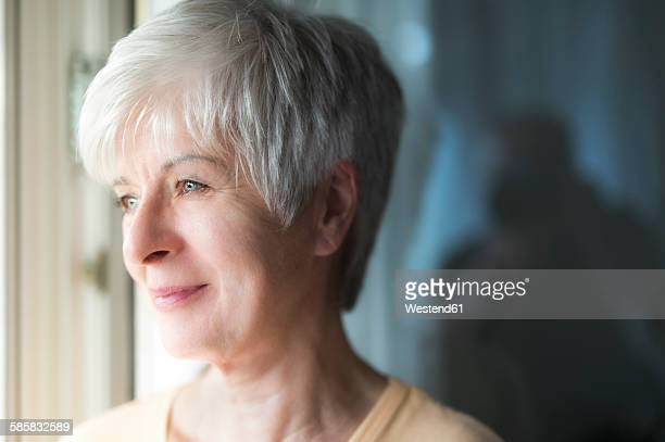 Portrait of smiling senior woman looking through window