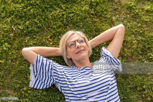 portrait of smiling senior woman lying in grass - liegen stock-fotos und bilder