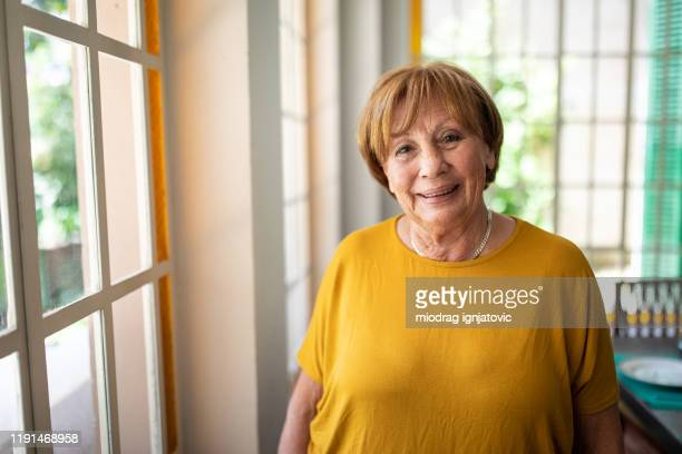 portrait of smiling senior woman near window - latin american and hispanic stock pictures, royalty-free photos & images