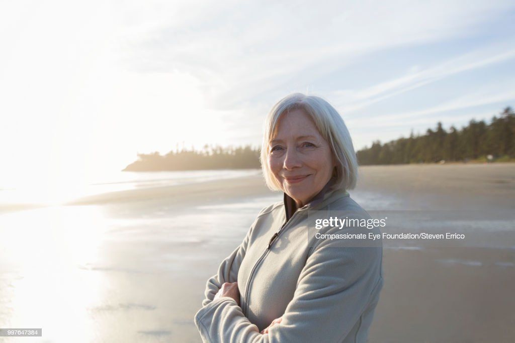 Portrait of smiling senior woman on beach at sunset : Stock Photo