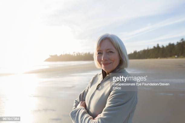 Portrait of smiling senior woman on beach at sunset