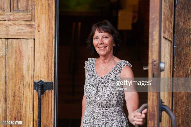 portrait of smiling senior woman opening door of language school - deurkozijn stockfoto's en -beelden
