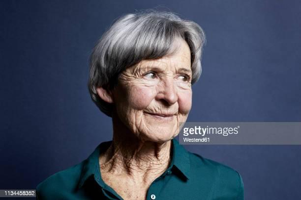 portrait of smiling senior woman - seniorinnen stock-fotos und bilder