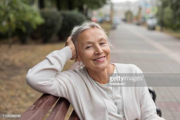 portrait of smiling senior woman relaxing on a bench - 65 69 jaar stockfoto's en -beelden