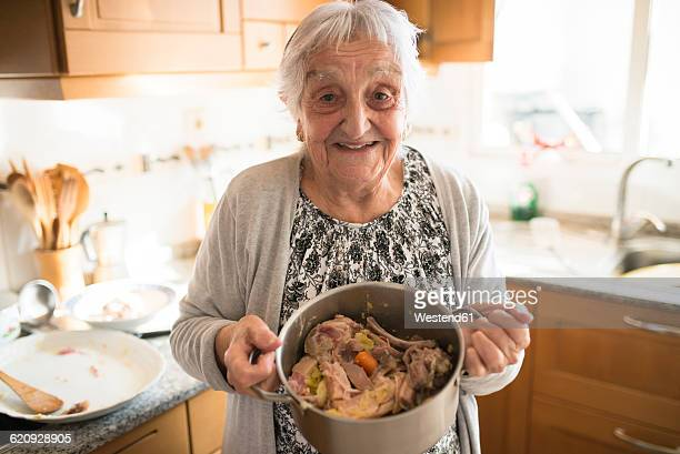 Portrait of smiling senior woman showing a cooking pot of Galician stew in the kitchen
