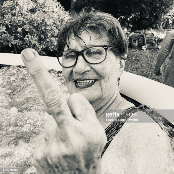 portrait of smiling senior woman showing obscene gesture - old lady middle finger stock pictures, royalty-free photos & images