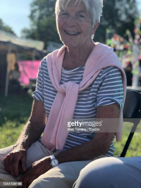 portrait of smiling senior woman sitting at backyard during sunny day - chesterton stock photos and pictures
