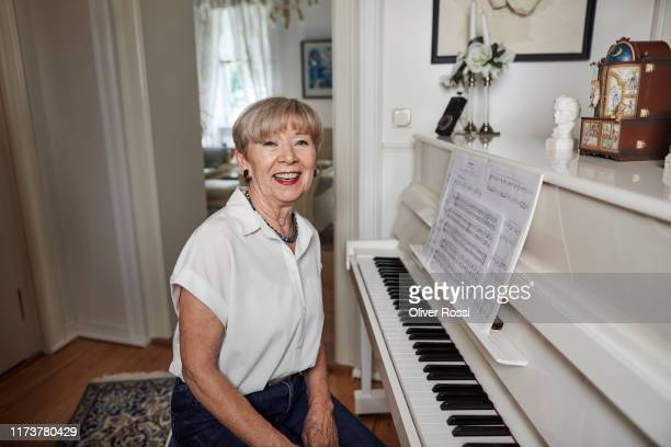 portrait of smiling senior woman sitting at the piano at home - lifestyle stock pictures, royalty-free photos & images