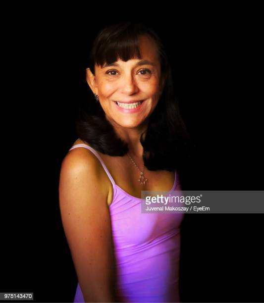 Portrait Of Smiling Senior Woman Standing Against Black Background