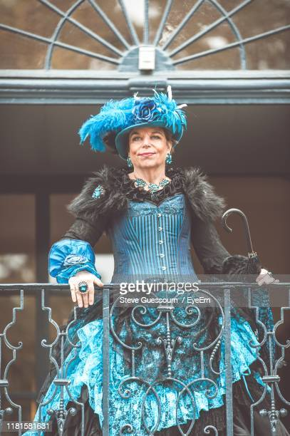portrait of smiling senior woman standing at railing - steve guessoum stockfoto's en -beelden
