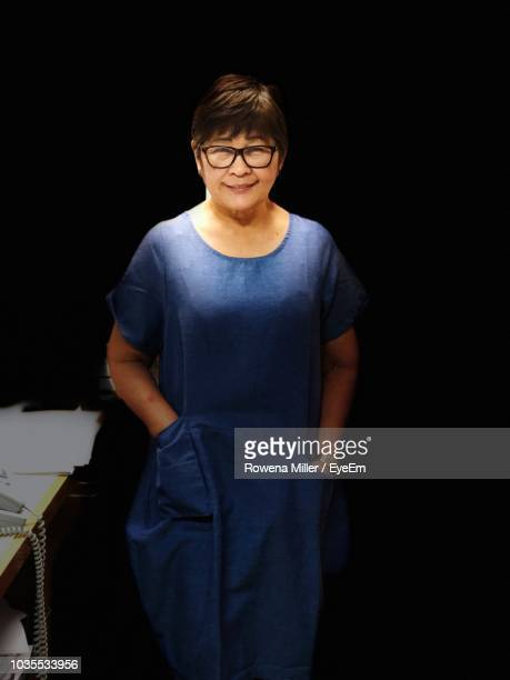 portrait of smiling senior woman standing in darkroom - rowena miller stock photos and pictures