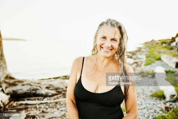 portrait of smiling senior woman standing on beach after swim on summer evening - 胸の谷間 ストックフォトと画像