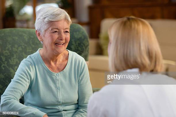 portrait of smiling senior woman talking with female doctor - visit stock pictures, royalty-free photos & images