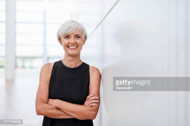 portrait of smiling senior woman wearing black dress leaning against a wall - vestido preto imagens e fotografias de stock