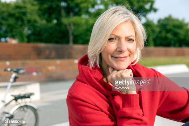 portrait of smiling senior woman wearing red hoodie outdoors - red coat stock pictures, royalty-free photos & images