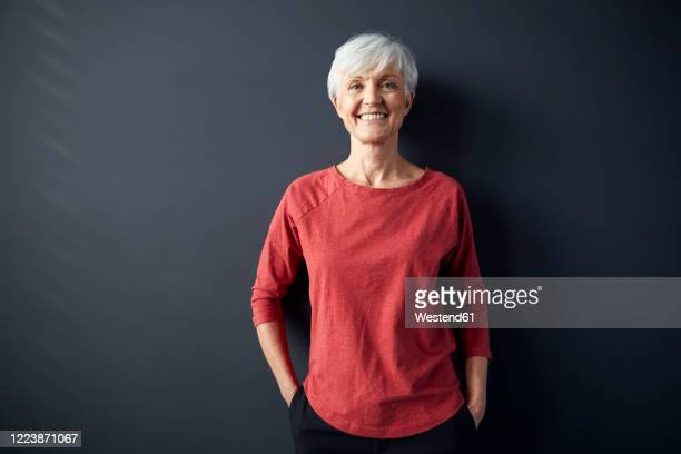 portrait of smiling senior woman wearing red shirt standing in front of grey wall - 60 64 years stock pictures, royalty-free photos & images