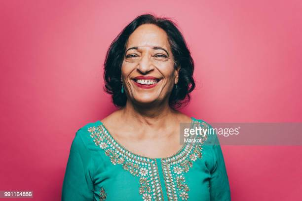 portrait of smiling senior woman wearing salwar kameez against pink background - cultura hindú fotografías e imágenes de stock
