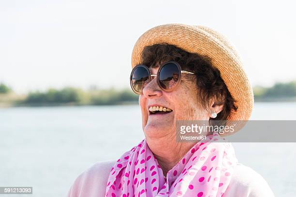 Portrait of smiling senior woman wearing sunglasses and summer hat