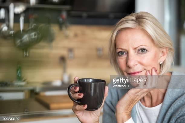 portrait of smiling senior woman with coffee mug in the kitchen - 60 64 jahre stock-fotos und bilder