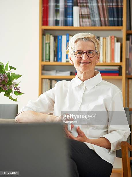 Portrait of smiling senior woman with cup of coffee at home