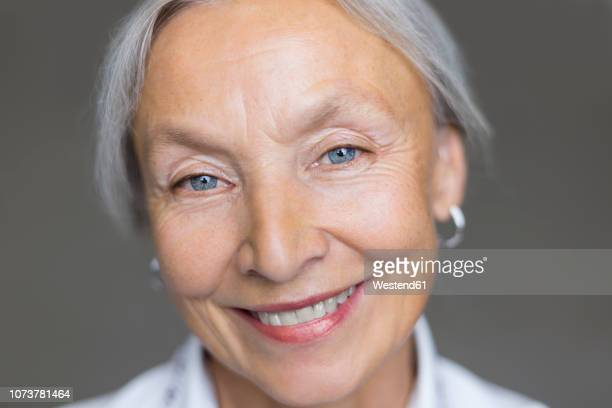 portrait of smiling senior woman with grey hair and blue eyes - one senior woman only stock pictures, royalty-free photos & images