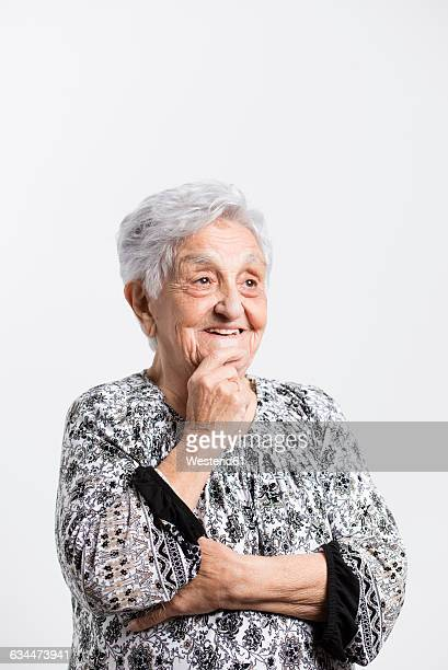 Portrait of smiling senior woman with hand on her chin in front of white background