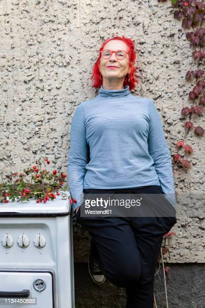 portrait of smiling senior woman with red dyed hair leaning against house front - cool und lässig stock-fotos und bilder