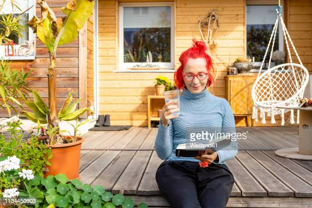 portrait of smiling senior woman with red dyed hair sitting on terrace in front of her house reading a book - older redhead stock pictures, royalty-free photos & images