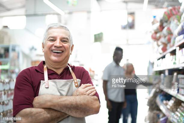portrait of smiling senior worker at wholesale - market retail space stock pictures, royalty-free photos & images